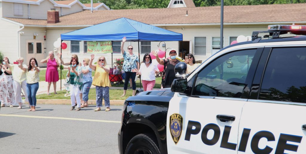 Good Shepherd's staff waving at the children during the 2020 drive by graduation.